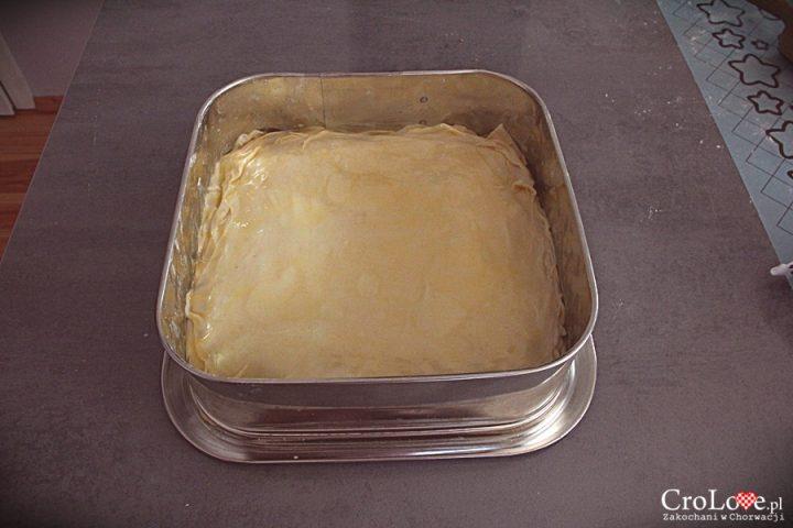 Warstwy ciasta układamy jedną na drugą, nakładając pomiędzy warstwę roztopionego masła